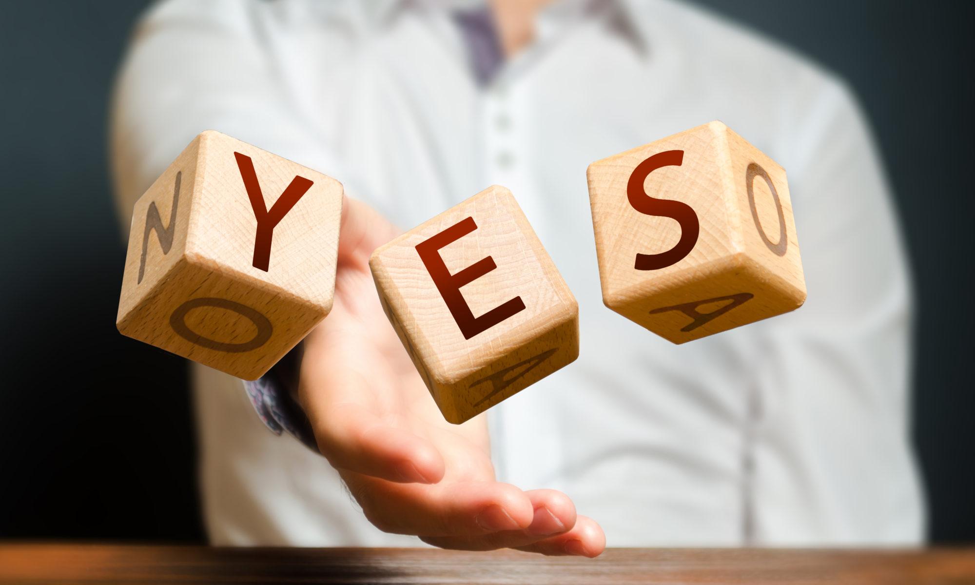 """איש זורק קוביות שמאייתות את המילה """"כן"""""""